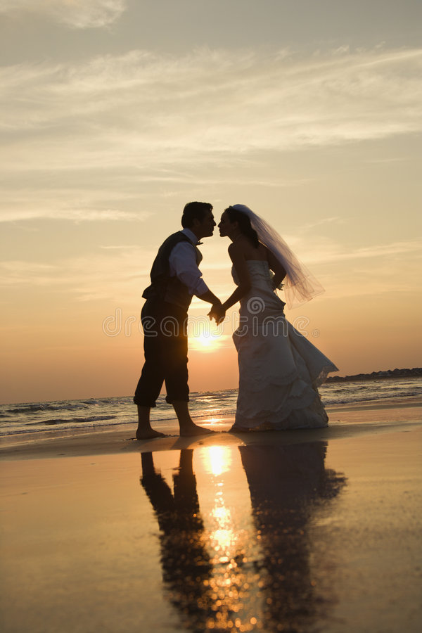 Bride and groom kissing on beach. royalty free stock photo