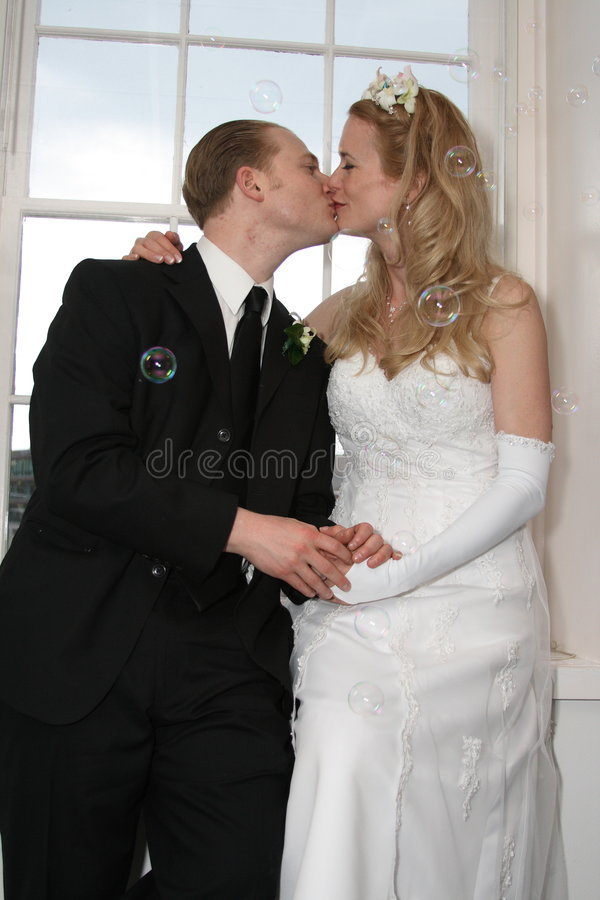 Bride And Groom Kissing With Bubbles Stock Photo