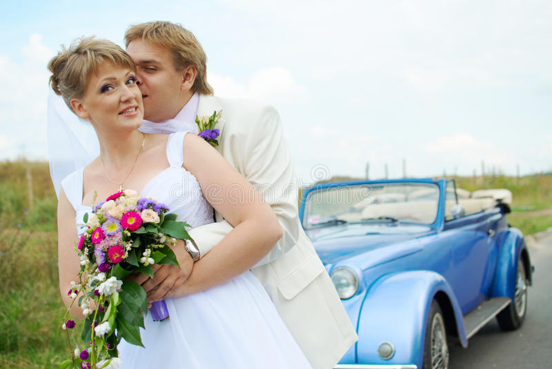 Bride and groom kissing in the car stock image
