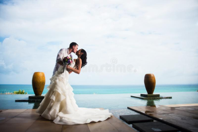 Bride and groom kissing on a clear Sunny day on a beautiful tropical beach stock photo