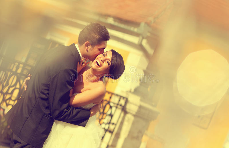 Bride and groom kissing and embracing in the city. Lovely day wedding royalty free stock photos