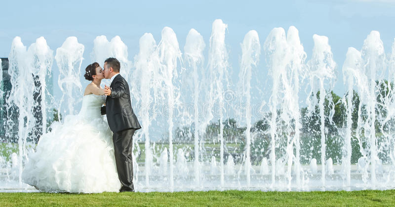 Bride and groom kissing in front of water spray fountain stock photo