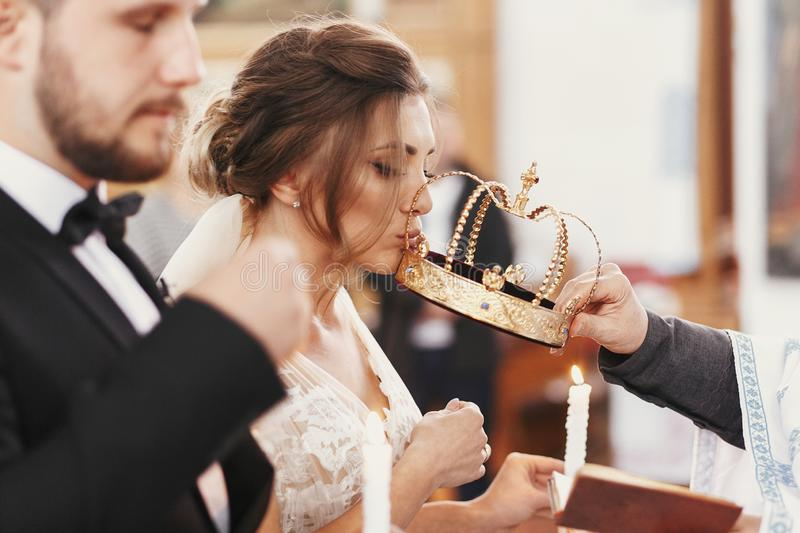Bride and groom kissing golden crowns from priest hand during we. Dding ceremony. Spiritual couple. Wedding matrimony in church. Emotional romantic moments royalty free stock photo