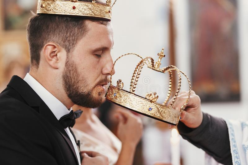 Bride and groom kissing golden crowns from priest hand during we. Dding ceremony. Spiritual couple. Wedding matrimony in church. Emotional romantic moments royalty free stock photography