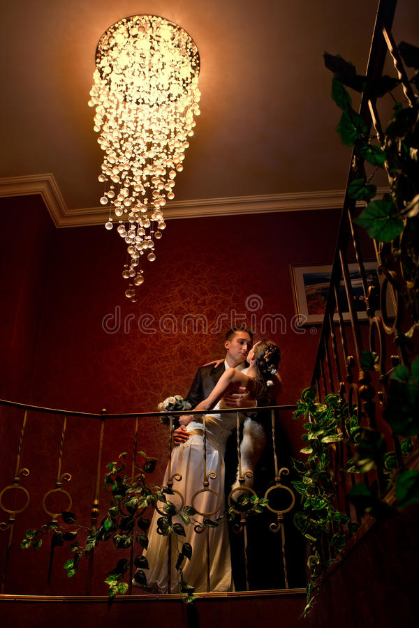 Bride and groom kissing in hotel stock photos