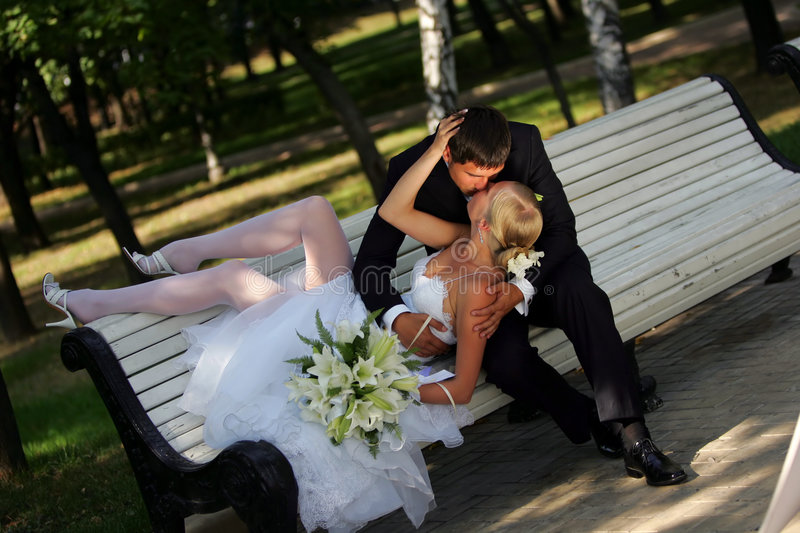 Bride and Groom Kissing on Park Bench royalty free stock photo