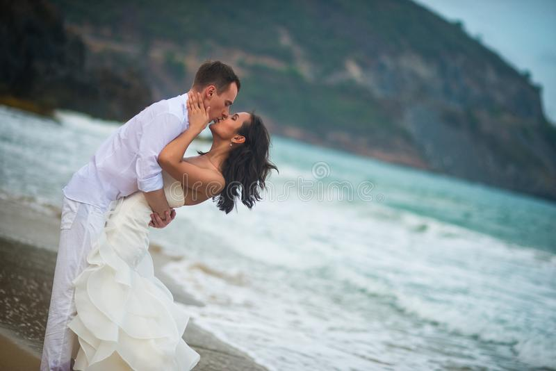 Bride and groom kissing by the sea. couple in love on a deserted beach. The bride and groom kissing by the sea. couple in love on a deserted beach stock photography