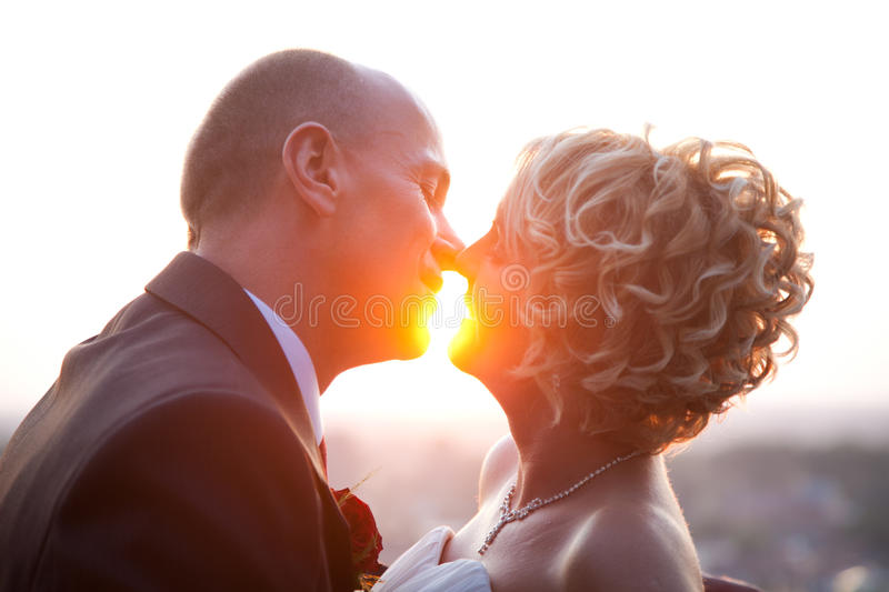 Bride and groom kissing at sunset. Happy bride and groom kissing outdoors at sunset stock photo