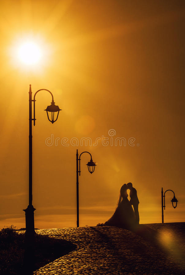 Bride and groom kissing at sunset. Beautiful scene with bride and groom kissing at sunset