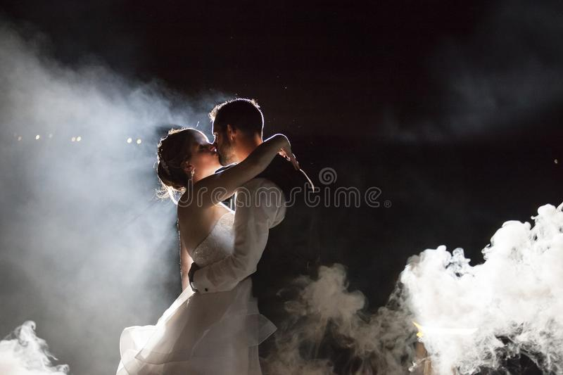 Bride and Groom kissing under fog at night royalty free stock photo