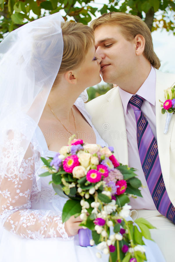 Bride and groom kissing under the tree royalty free stock photo