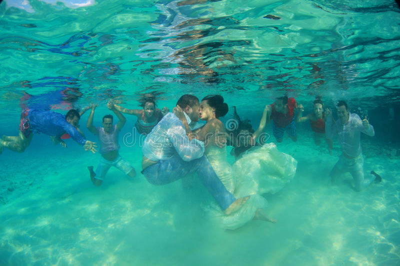 Bride and groom kissing underwater with many couples in the background royalty free stock photography