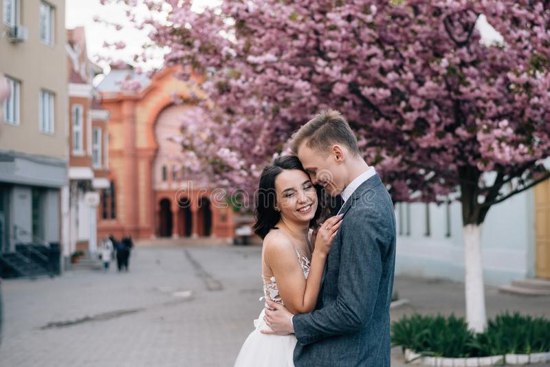 The bride and groom laugh on the street. Wedding dress and groom`s suit royalty free stock images