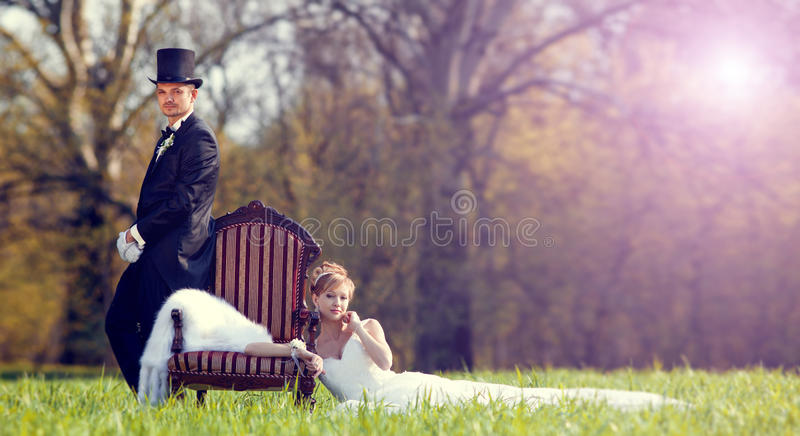 The bride and groom on the lawn in the forest. Outdoors stock images