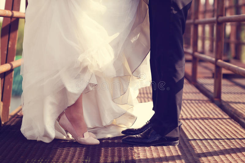 Bride and groom legs on a bridge royalty free stock photo