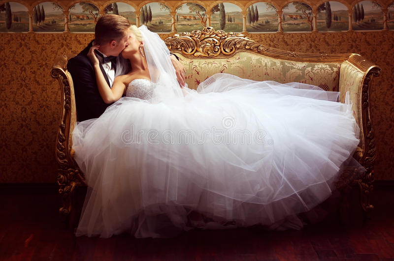Bride and groom on a luxury hotel, kissing on a sofa royalty free stock photo