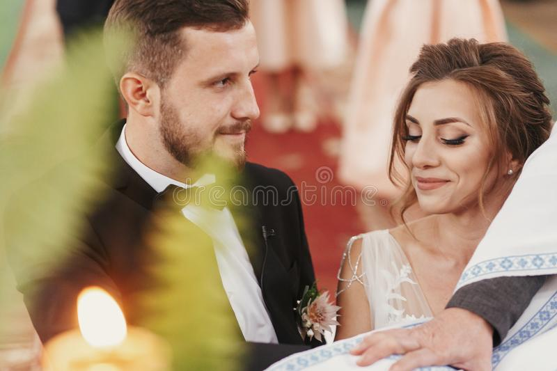 Bride and groom making oaths and priest holding their hands on. Holy Bible. Wedding matrimony in church. Exchanging vows. Emotional romantic moments stock photography