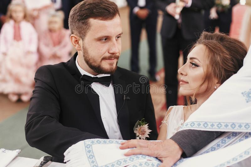 Bride and groom making oaths and priest holding their hands on. Holy Bible. Wedding matrimony in church. Exchanging vows. Emotional romantic moments royalty free stock image