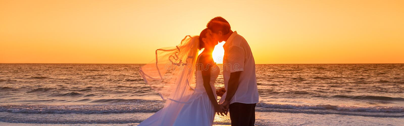 Bride and Groom Married Couple Sunset Beach Wedding Panorama. Married couple, bride and groom, kissing at sunset or sunrise on a beautiful tropical beach wedding stock images