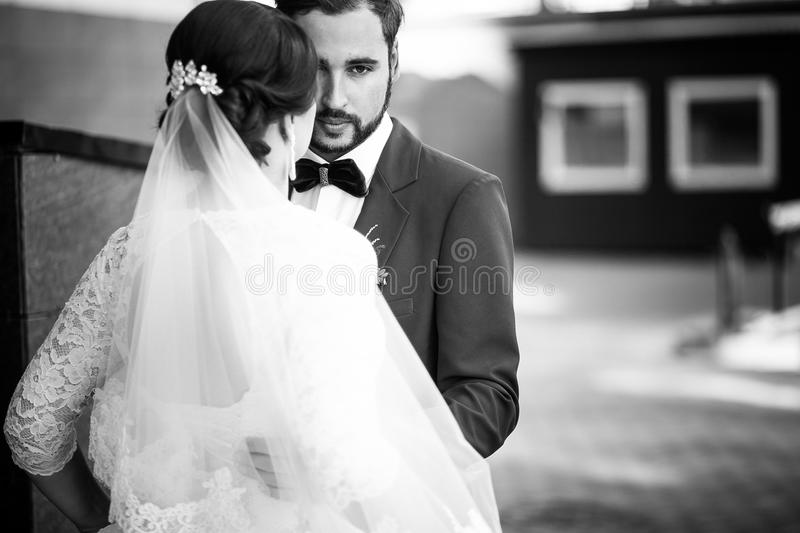 Bride and groom monochrome portrait. The man has a serious look, wedding retro classic. stock photography