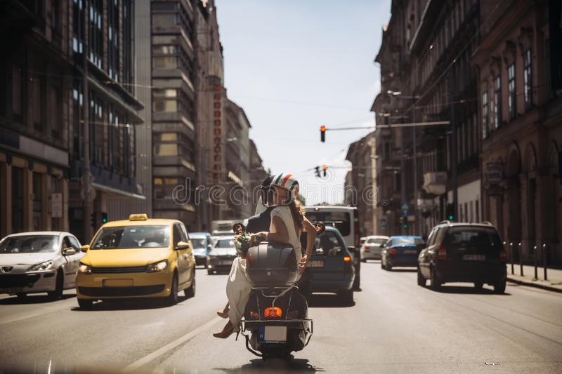 Bride and groom on a moped on their wedding day stock photography
