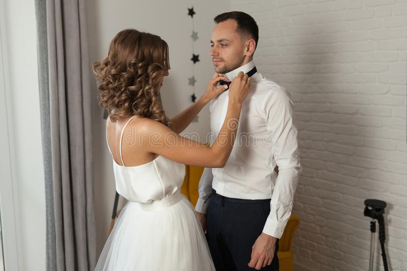 The bride and groom in the morning at the hotel on a wedding day. Dressing a newly-married couple Woman help fixing bowtie to royalty free stock image