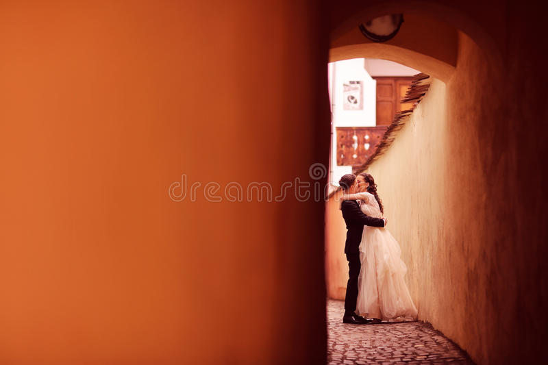 Bride and groom on a narrow street. Embracing stock photography
