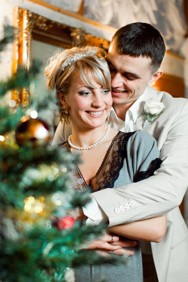 Bride and groom near christmas tree
