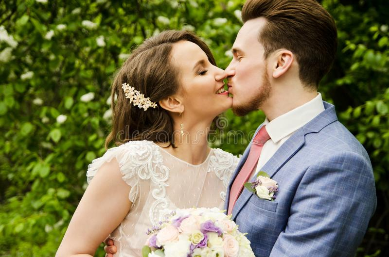 Bride and groom in a park kissing.couple newlyweds bride and groom at a wedding in nature green forest are kissing photo portrait. stock photos