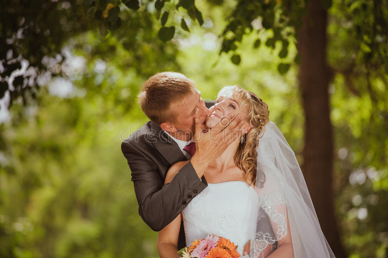 Bride and groom in a park kissing royalty free stock photography