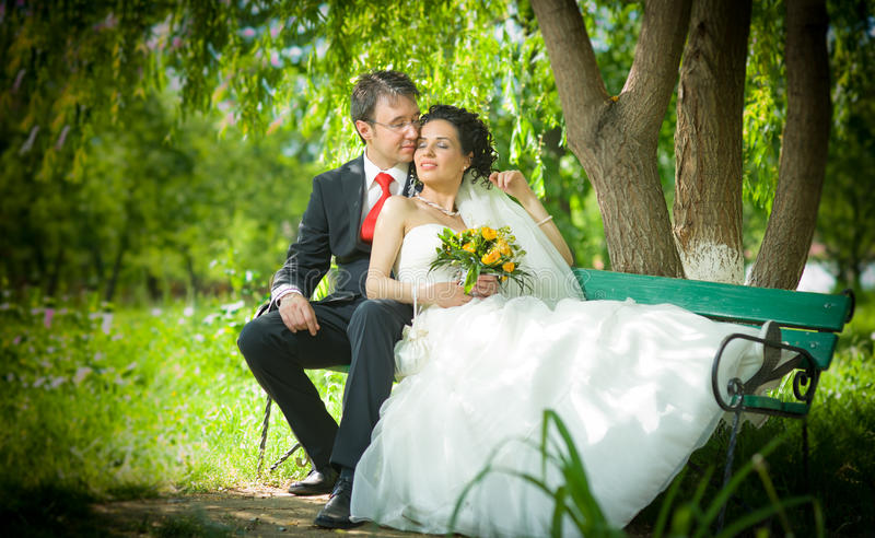 Bride and groom in a park sit on the bench stock images