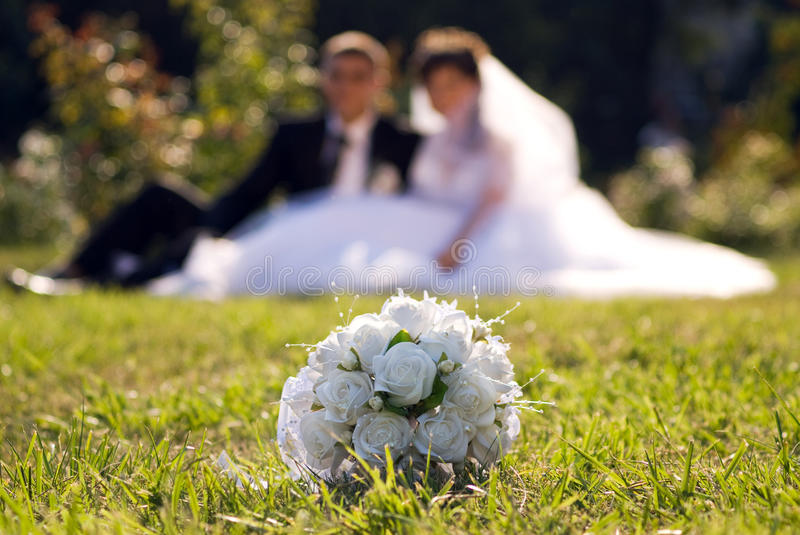 Bride and groom in the park (warmer). Bride and groom in the park (out of focus). Accent on the flowers bouquet, on the first plan. A higher vanish point royalty free stock photography