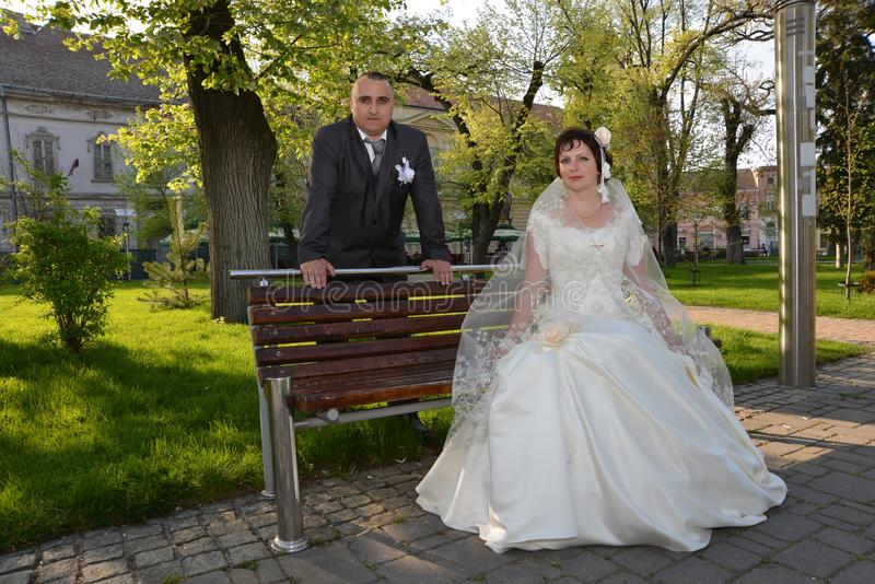 Bride and groom in the park. A woman sits on a bench, a man rests his hands on the back of the bench. Silk dress champagne color royalty free stock photography