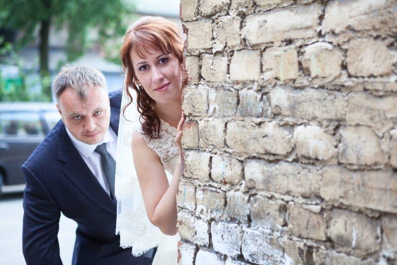 Bride and groom peek around corner of brick wall, copyspace. Bride and groom peek around the corner of brick wall, copyspace royalty free stock photos