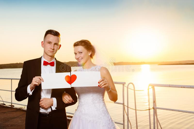 Bride and groom on the pier at sunset. royalty free stock photography