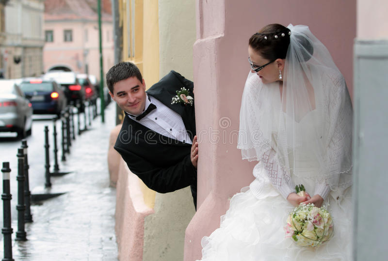 Bride and groom playing hide and seek royalty free stock photos