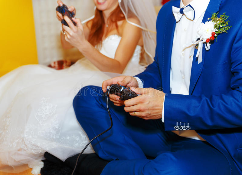 Bride and groom playing together videogames with joysticks - gaming and wedding concept. royalty free stock photos