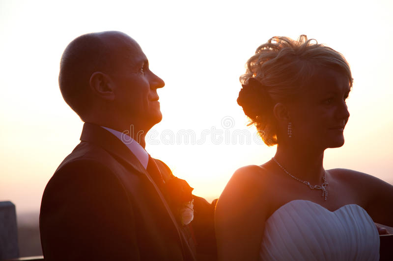 Bride and groom portrait at sunset. Happy bride and groom together outdoors at sunset royalty free stock photography