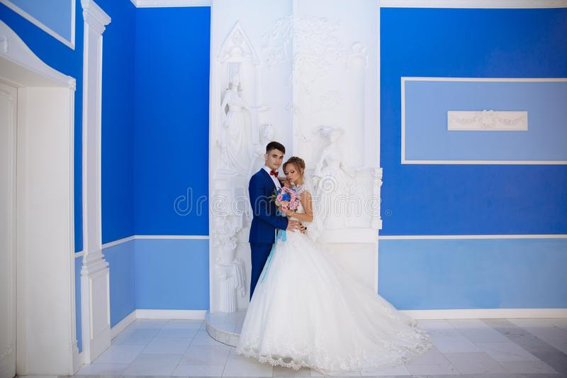 The bride and groom are posing for a photo in a huge blue hall with white columns. The color of the groom`s costume is stock image