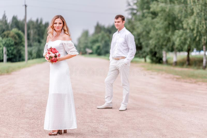 Bride and groom posing on the road stock photos