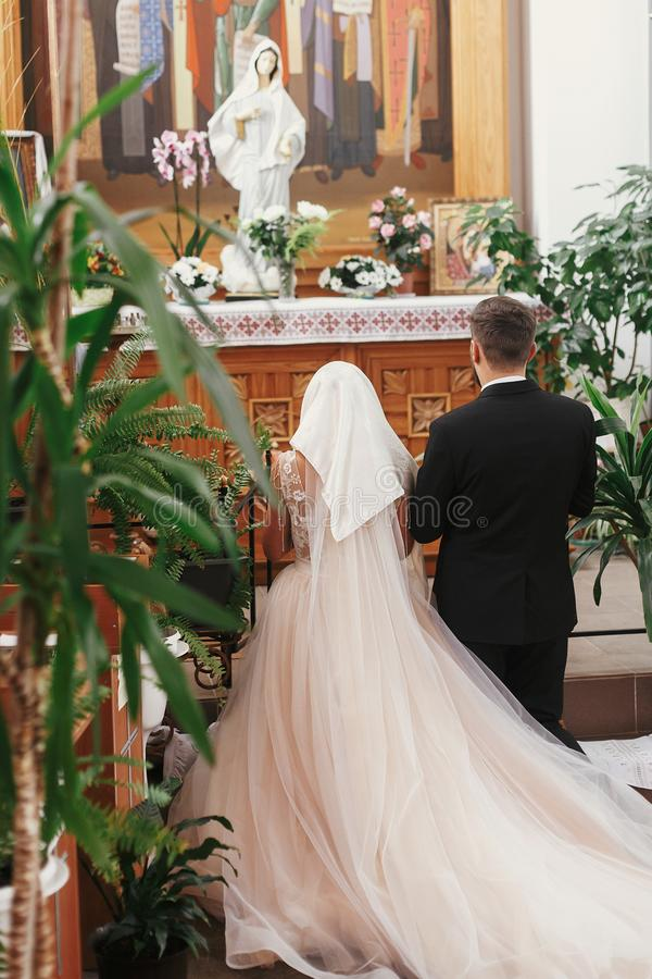 Bride and groom praying, standing on knees at Virgin Mary statue. During wedding ceremony. Spiritual couple. Wedding matrimony in church. Emotional romantic stock images