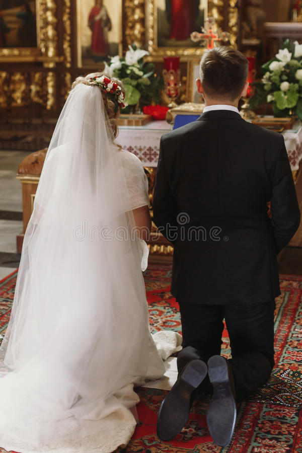 Bride and groom praying at wedding ceremony in church, handsome stock image