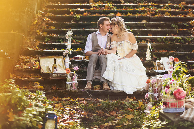 The bride and groom in retro style hugging on stone steps at autumn forest, surrounded by wedding decor. stock photo