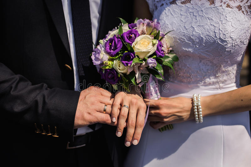Bride and groom with rings on their hands, male and female hand with wedding rings. Wedding ceremony, together forever, wedding flowers, wedding bouquet, hands stock photography
