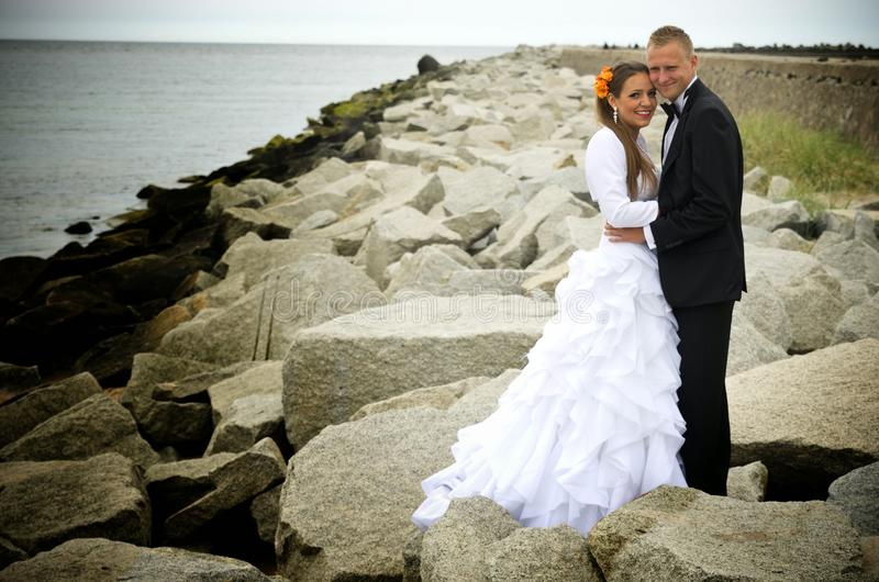 Bride and groom on rocks, Baltic Sea royalty free stock photos