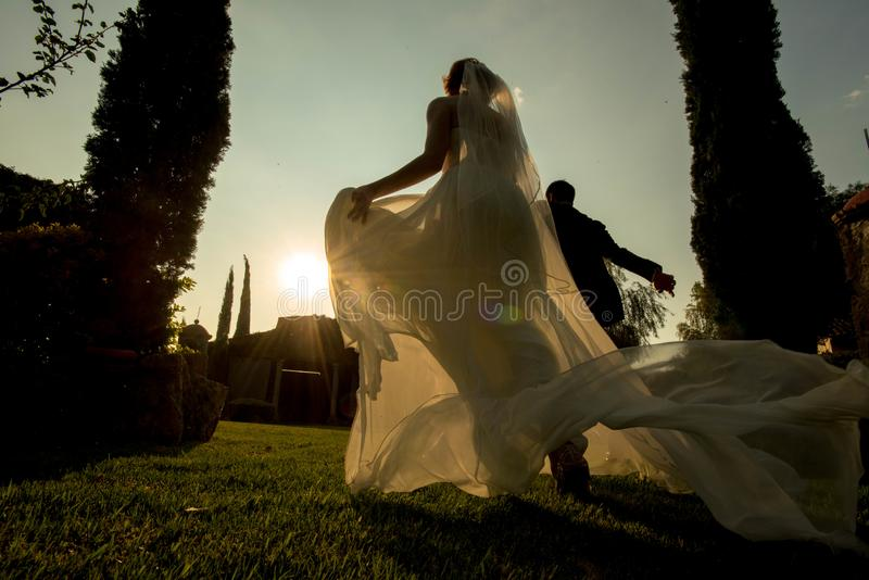 Bride and groom running away at sunset, garden wedding at sunset, hacienda wedding in Mexico royalty free stock photography