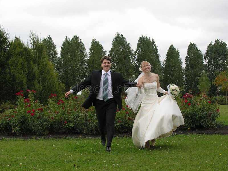 Bride and groom running from trees royalty free stock photo