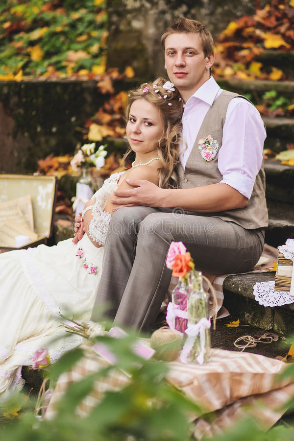 The bride and groom in a rustic style sitting on stone steps at sunny autumn forest, surrounded by wedding decor. royalty free stock photography
