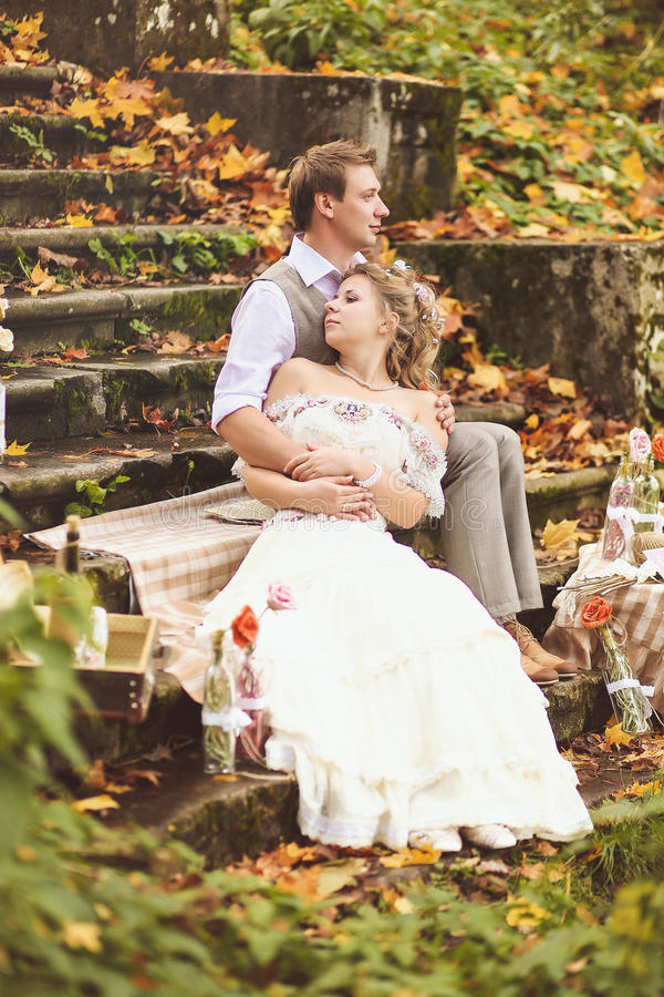The bride and groom in a rustic style sitting on stone steps at sunny autumn forest, surrounded by wedding decor. stock photography
