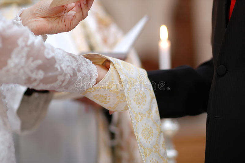 Bride and groom's hands and priest's cassock. Wedding: bride and groom's hands wrapped in priest's cassock royalty free stock photography